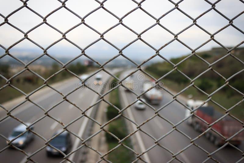 Близкая поднимающая вверх загородка ячеистой сети Движение на дороге на предпосылке стоковые фото