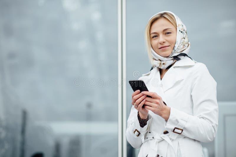 Близкая поднимающая вверх молодая женщина взгляда в большом городе используя телефон с экземпляром s стоковая фотография