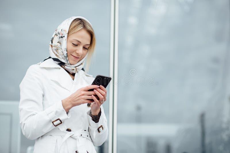 Близкая поднимающая вверх молодая женщина взгляда в большом городе используя телефон с экземпляром s стоковое изображение rf