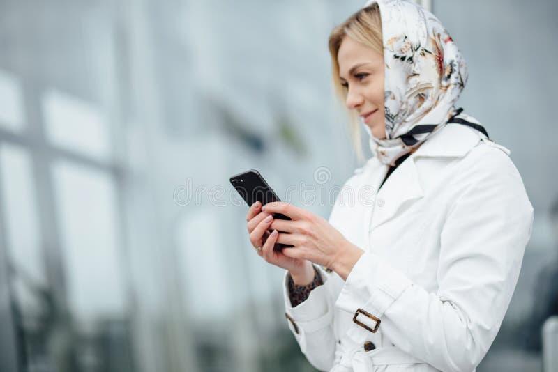Близкая поднимающая вверх молодая женщина взгляда в большом городе используя телефон с экземпляром s стоковые фото