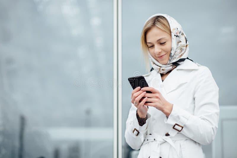 Близкая поднимающая вверх молодая женщина взгляда в большом городе используя телефон с экземпляром s стоковые изображения