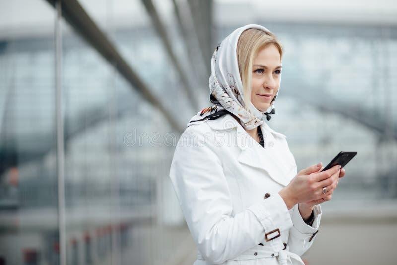 Близкая поднимающая вверх молодая женщина взгляда в большом городе используя телефон с экземпляром s стоковые фотографии rf