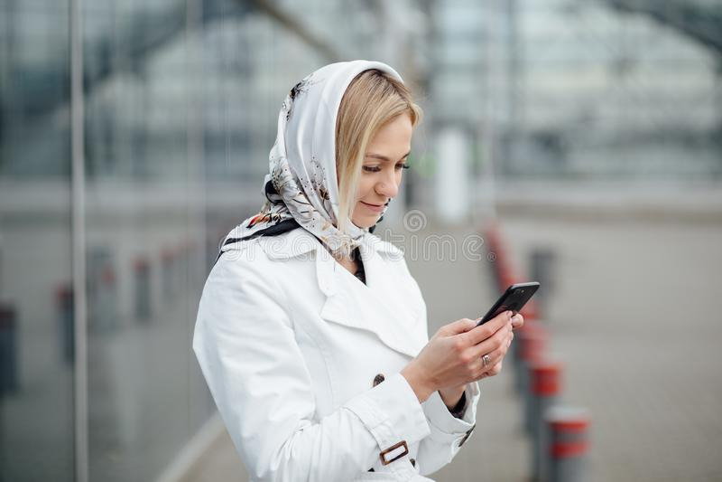 Близкая поднимающая вверх молодая женщина взгляда в большом городе используя телефон с экземпляром s стоковое фото rf