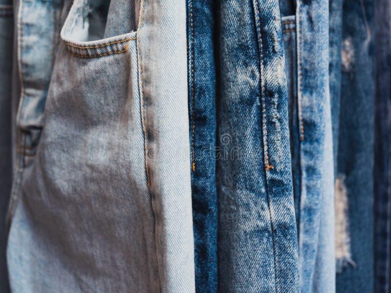 Близкая поднимающая вверх строка много голубых джинсов висит стоковые фото
