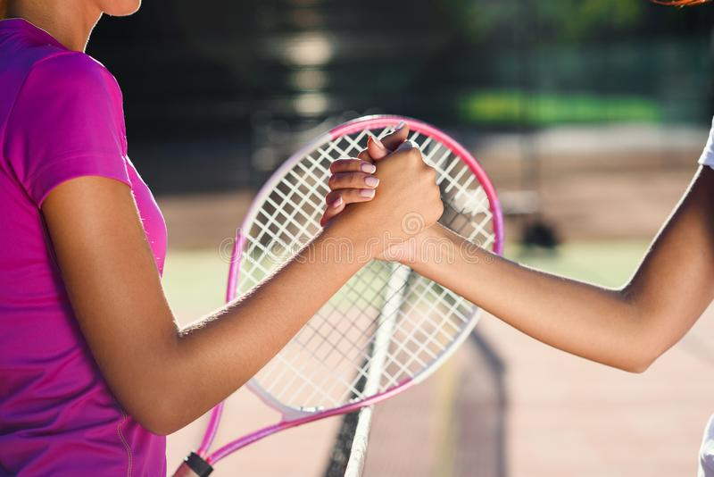 Близкая поднимающая вверх съемка 2 молодых женских теннисистов тряся руки над сетью Дружелюбное рукопожатие после конца  стоковые фотографии rf