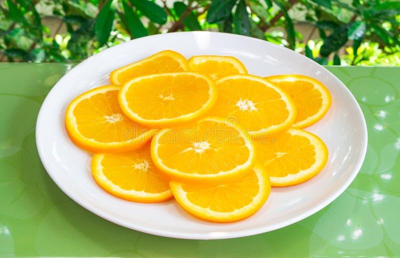 Близкая поднимающая вверх съемка оранжевых кусков на белой плите Здоровая и вегетарианская еда стоковое изображение rf