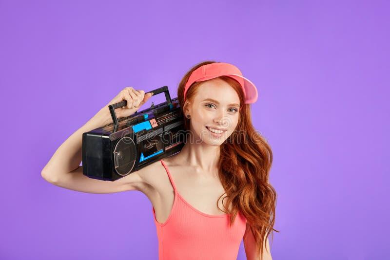 Близкая поднимающая вверх съемка рыжеволосой молодой женщины с игроком кассеты на ее плече стоковые фото