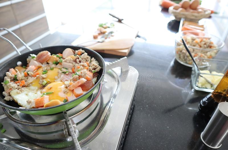 Близкая поднимающая вверх съемка яя зажаренного лотка с семенить свининой и сосиской на storve стоковая фотография