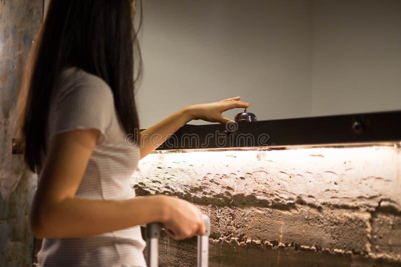 Близкие поднимающие вверх женщины вызывают прием гостиницы на встречном столе с пальцем для нажатия колокола в гостинице лобби ко стоковые фото