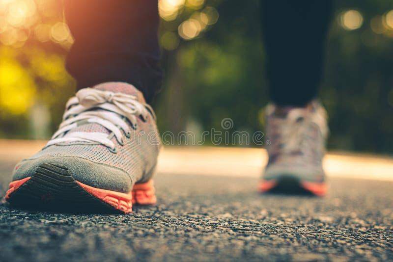 Близкие поднимающие вверх женщины ноги бегут ноги на дороге в здоровье разминки стоковая фотография rf