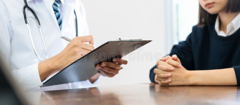 Близкий вверх доктора и рук пациента сидя на таблице и говорить об условии пациента стоковые изображения rf
