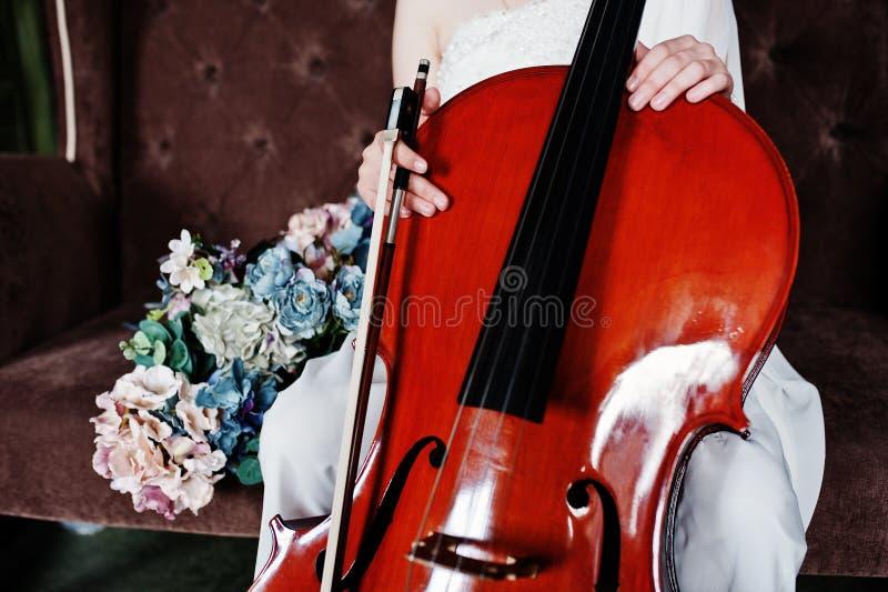 Близкий вверх музыканта gilrl в белом платье с двойным басом сидя на коричневой винтажной софе стоковая фотография