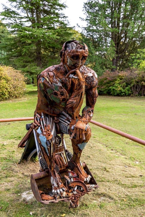 Близкий взгляд скульптуры Re-мыслителя сделанной ненужных стальных объектов и повышать для того чтобы повторно использовать польз стоковые фотографии rf