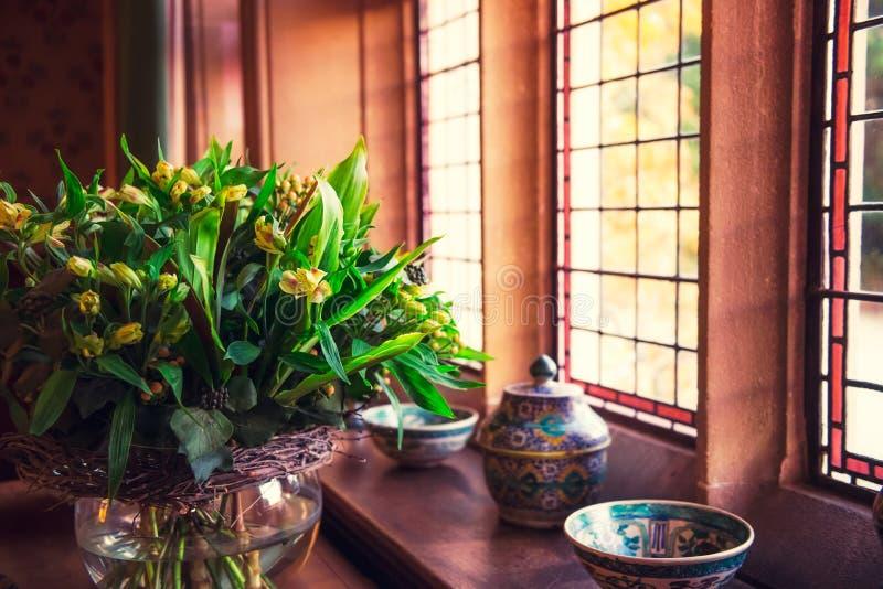 Близкий поднимающий вверх букет свежих желтых цветков в стеклянной вазе около деревянного окна с керамическими средневековыми блю стоковые фотографии rf