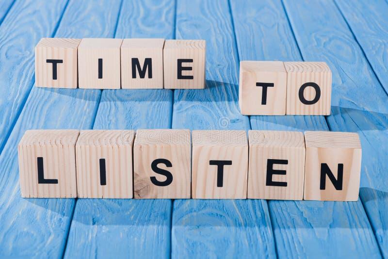 близкий поднимающий вверх взгляд аранжированных деревянных блоков во время слушать фраза на сини стоковое фото