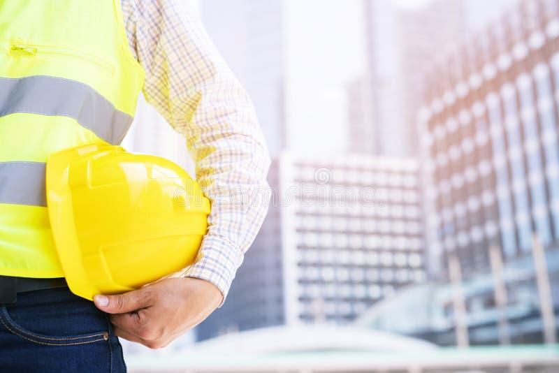 Близкий поднимающий вверх взгляд задней стороны проектировать мужскую стойку рабочий-строителя держа шлем безопасности желтый стоковое изображение
