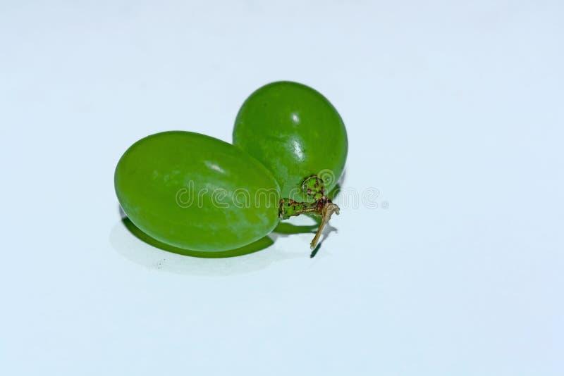 Близкий поднимающий вверх взгляд 2 зеленых виноградин на белой предпо стоковые изображения rf