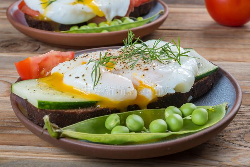 Близкий поднимающий вверх взгляд краденного яйца на сэндвиче с луком и горохами и томатом на деревянной предпосылке стоковые фото