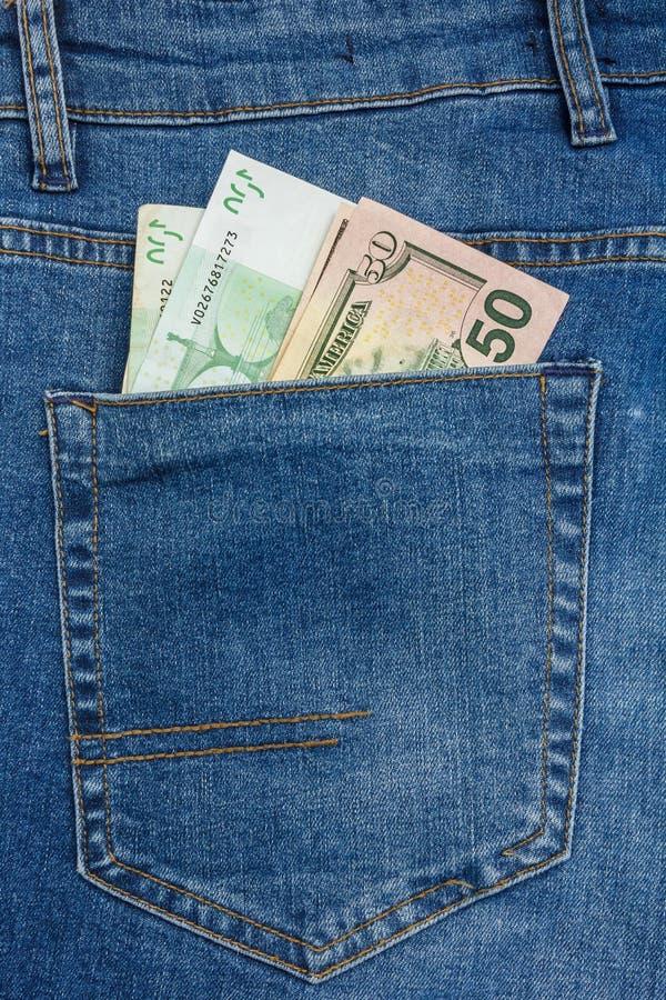 Близкий поднимающий вверх взгляд к банкнотам 100 евро и 50 долларов вставляя вне из кармана голубых джинсов стоковая фотография