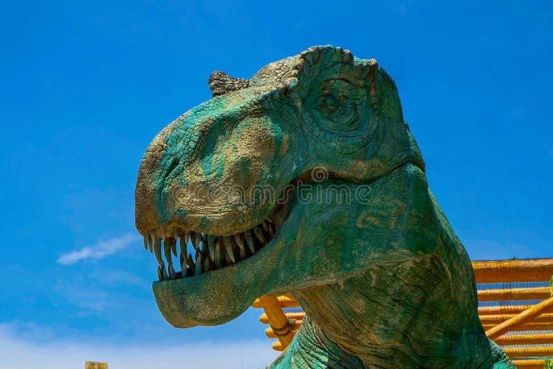 Близкий поднимающий вверх взгляд к голове раскрывать-рта динозавра На предпосылке голубого неба стоковые фотографии rf