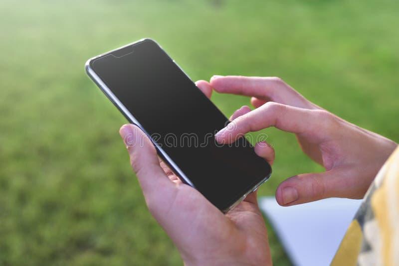 Близкий поднимающий вверх взгляд мужских рук печатая текстовое сообщение outdoors Молодой бизнесмен пишет sms стоковые изображения
