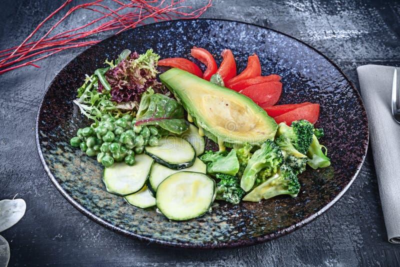 Близкий поднимающий вверх взгляд на зеленом салате с авокадоом в послуженный в черной текстурированной плите на темной предпосылк стоковые фото