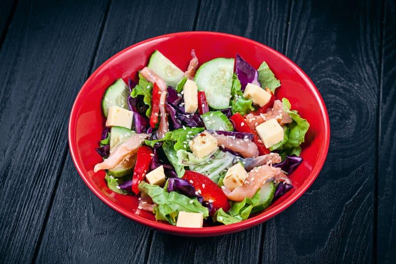 Близкий поднимающий вверх взгляд на свежем домодельном салате с семгами, томатом, огурцом, салатом и сыром E Морепродукты на обед стоковые изображения