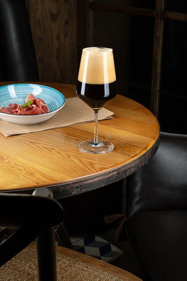 Близкий поднимающий вверх взгляд на холодном темном пиве ремесла в стекле с закуской на баре на таблице Cocnept изображения Адвок стоковые фото