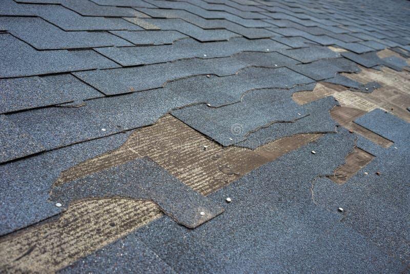 Близкий поднимающий вверх взгляд повреждения крыши гонт битума которому нужен ремонт стоковые изображения