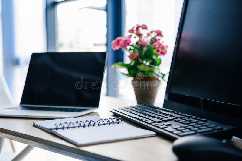 близкий поднимающий вверх взгляд пустого учебника, ноутбука, цветков в баке, компьютера, клавиатуры компьютера и мыши компьютера стоковое фото rf