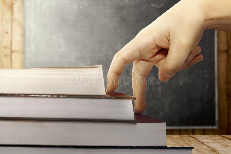 Близкий поднимающий вверх взгляд руки пальцев взбирается шаги книги на деревянный стол с предпосылкой классн классного стоковые фото