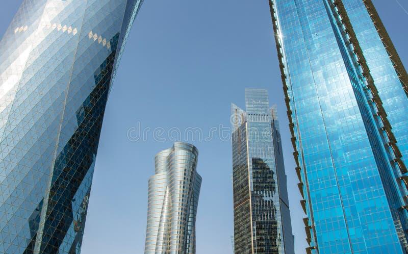 Близкий поднимающий вверх взгляд современных небоскребов со стеклянным фасадом финансовым и деловым центром в Дохе, Катаре стоковая фотография rf