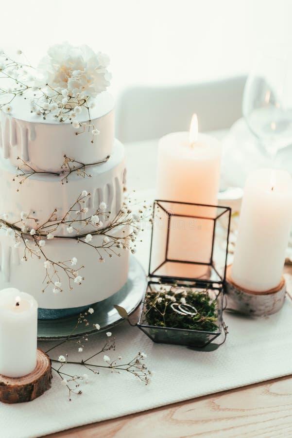 близкий поднимающий вверх взгляд стильной сервировки стола со свечами и обручальными кольцами стоковая фотография
