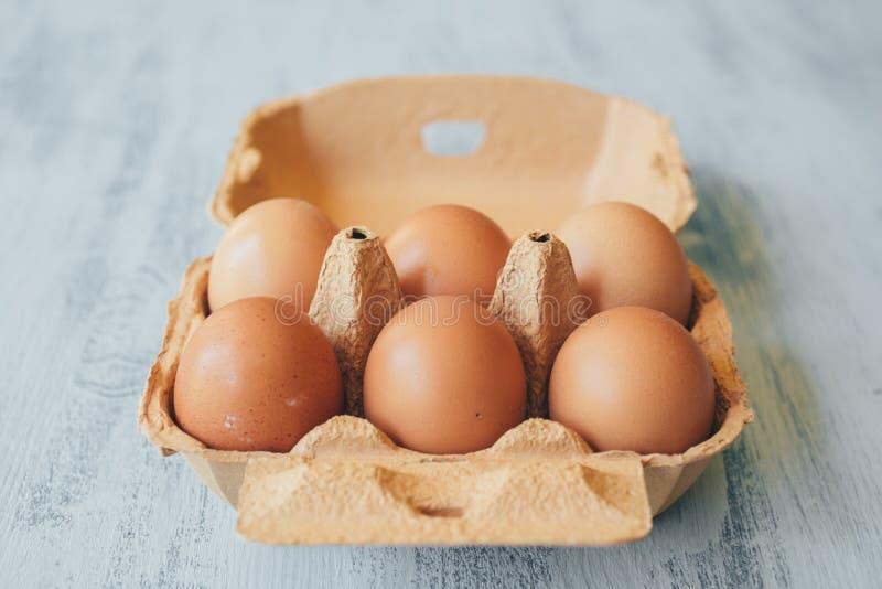 Близкий поднимающий вверх взгляд сырцовых яя цыпленка в коробке яйца на белом деревянном столе стоковые фотографии rf