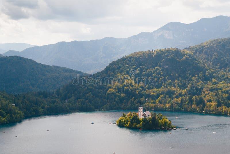Близкий поднимающий вверх вид с воздуха кровоточенного острова на озере кровоточенном в Словении окружил горами и лесами стоковая фотография