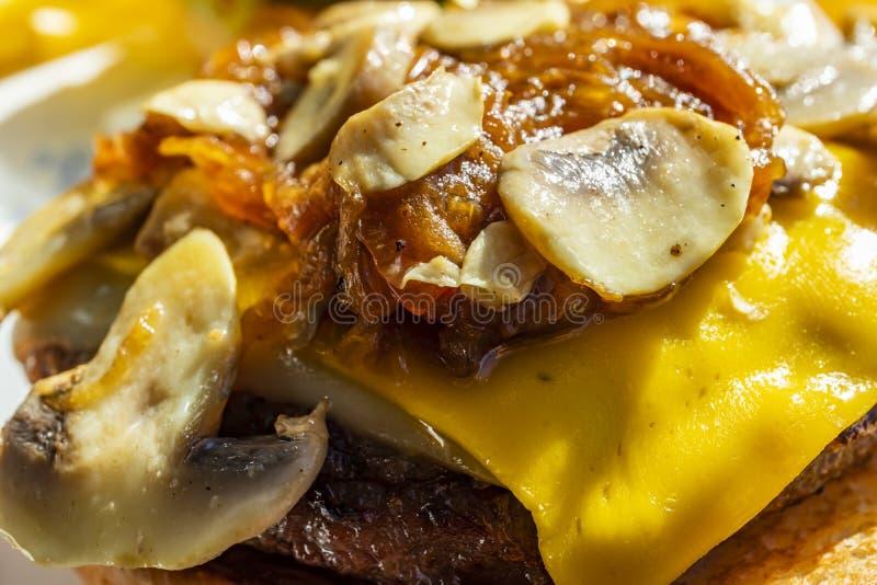 Близкий поднимающий вверх гамбургер с грибами и сыром чеддера стоковое фото