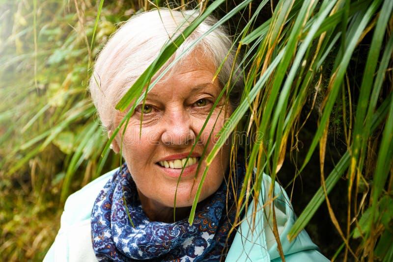 Близкий поднимающий вверх главный портрет красивой пожилой женщины с сияющим серым положением волос близко к траве стоковое фото rf
