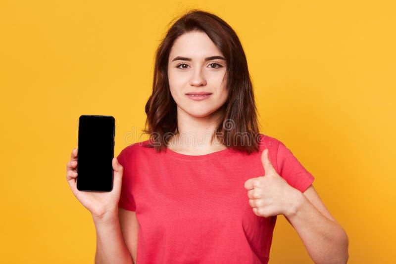 Близкий поднимающий вверх портрет красивого телефона удерживания женщины с пустым экраном и показывать знак с другой рукой, девуш стоковые фото