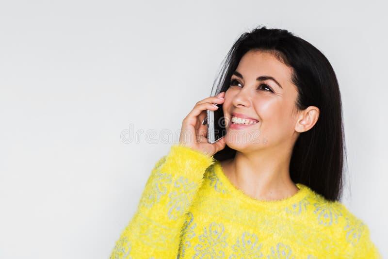 Близкий поднимающий вверх портрет красивой молодой счастливой женщины с умным телефоном, нося желтым свитером, с довольно зубасто стоковые фотографии rf