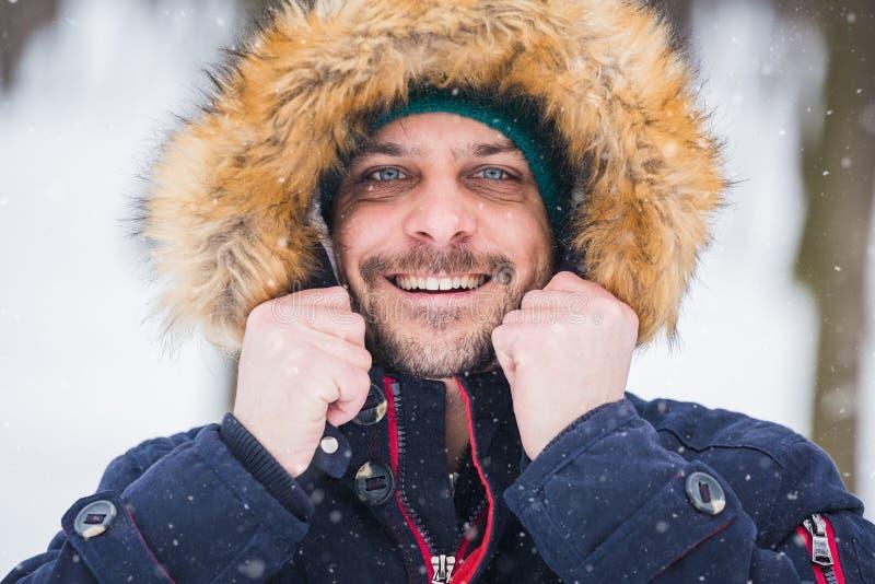 Близкий поднимающий вверх портрет молодого человека против парка предусматриванного с предпосылкой снега стоковое фото