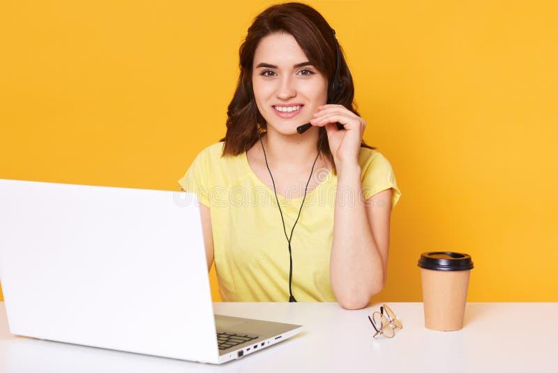 Близкий поднимающий вверх портрет молодой коммерсантки в наушниках с микрофоном перед раскрытым ноутбуком, сидит на белой таблице стоковые изображения