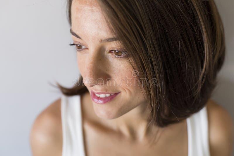 Близкий поднимающий вверх портрет привлекательной беременной женщины сидя в кровати и держа ее живот Последние месяцы беременност стоковая фотография