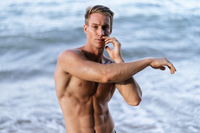 Близкий поднимающий вверх портрет сексуального мышечного нагого человека представляя на пляже стоковое изображение rf