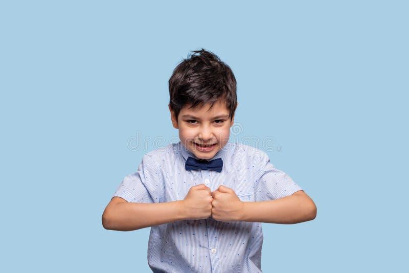 Близкий поднимающий вверх портрет a смешного мальчика нося голубую рубашку с бабочкой обхватывая его кулаки в воюя moodon против  стоковая фотография rf