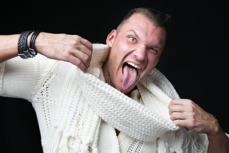 Близкий поднимающий вверх портрет смешного человека в свитере и шарфе показывает его язык против темной предпосылки стоковое изображение rf