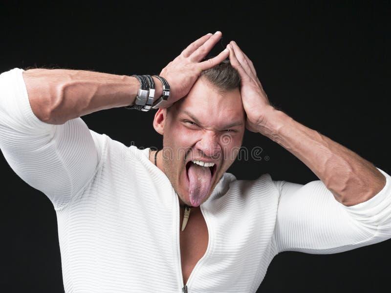Близкий поднимающий вверх портрет смешного человека в свитере и шарфе показывает его язык против темной предпосылки стоковые изображения rf