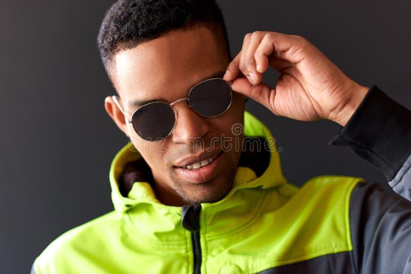 Близкий поднимающий вверх портрет стильного Афро-американского человека усмехаясь и смотря через солнечные очки зеркала стоковое изображение rf