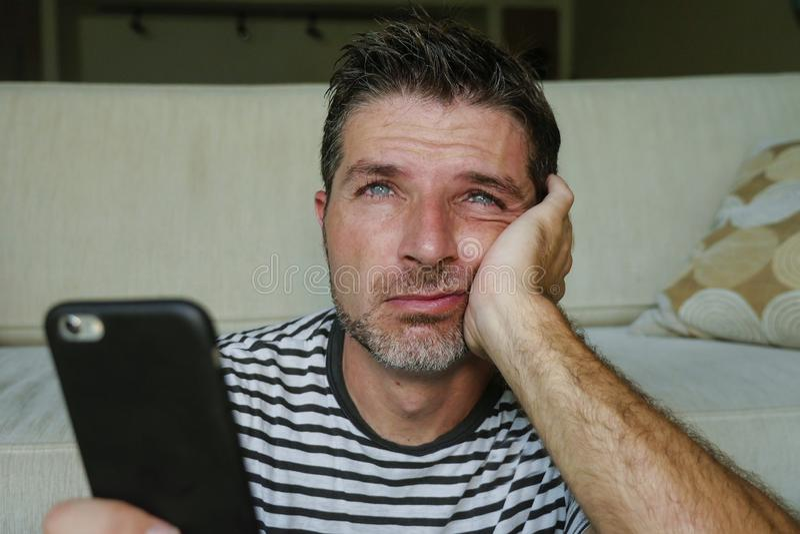 Близкий поднимающий вверх портрет стороны молодого привлекательного и усиленного человека используя смущенный мобильный телефон о стоковые изображения rf