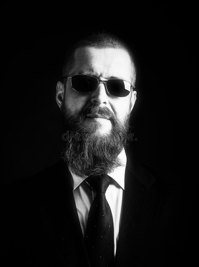 Близкий поднимающий вверх портрет студии бородатого мужчины хипстера в солнечных очках над темной предпосылкой низкие ключ на чер стоковое изображение