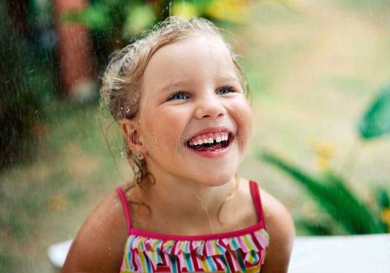 Близкий поднимающий вверх портрет счастливой милой маленькой девочки насладиться дождем лета стоковое фото